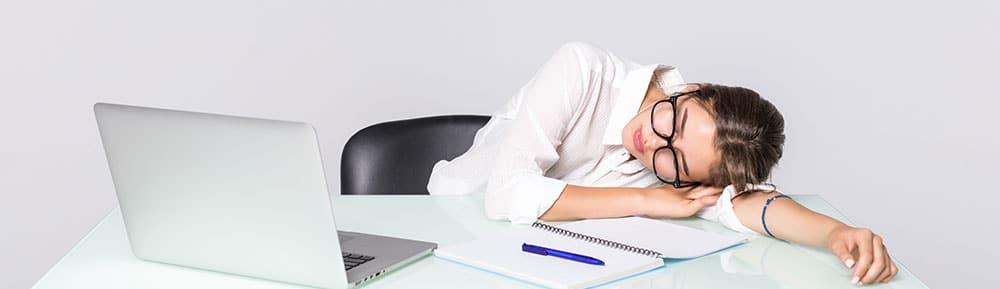 Junge brünette Frau mit Brille liegt auf dem Tisch und ist als Folge einer Übersäuerung träge und müde
