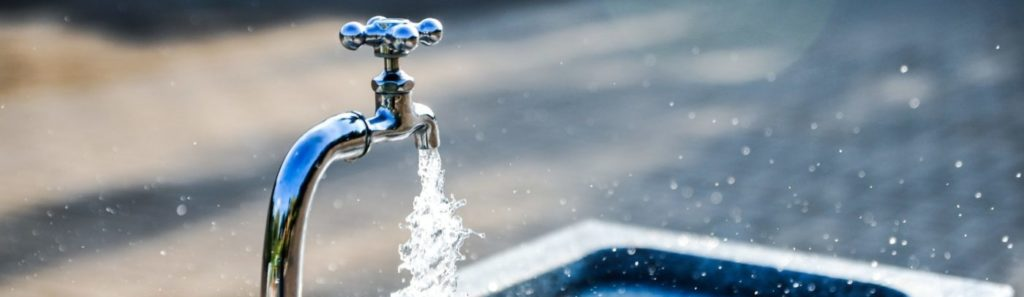 Das Bild zeigt einen Wasserhahn auf einem öffentlichen Platz aus dem Wasser läuft.