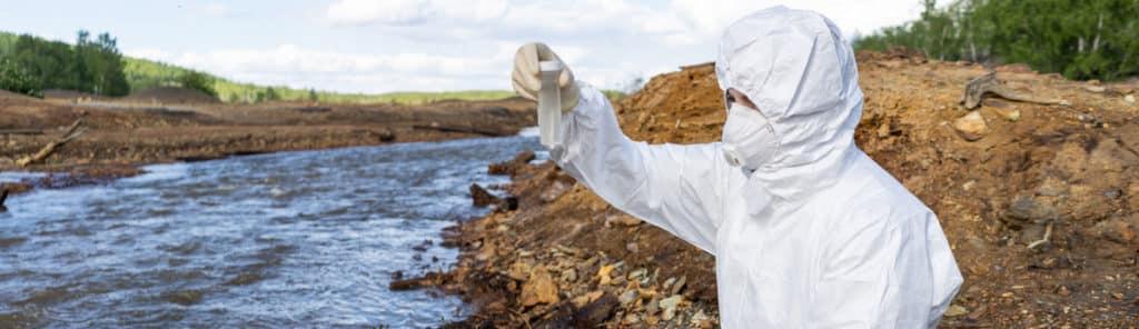 Person in weißem Schutzanzug nimmt eine Wasserprobe zur Messung der Nitratbelastung im Wasser