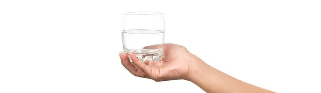 Hand mit Wasserglas auf weißen Hintergrund präsentiert Osmosewasser